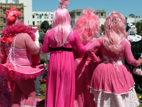 backsides of 4 men dressed in pink dresses with pink hair
