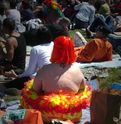 Back of woman with orange hair sundress and feather boa