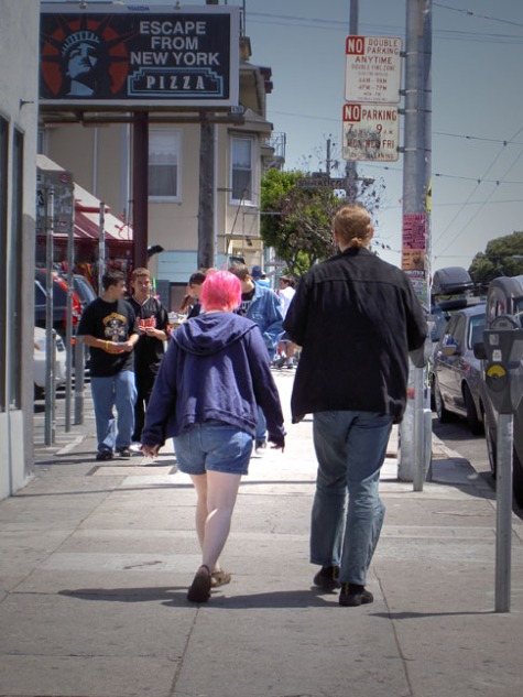 couple walking on Haight Street; woman has pink hair and white legs