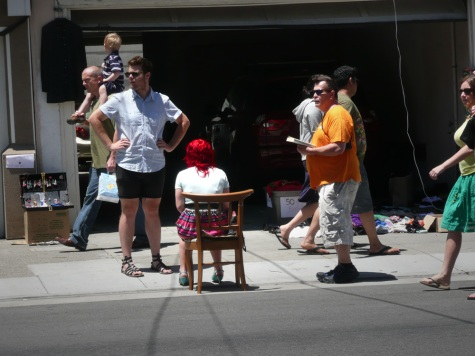 Red haired woman sitting in chair on sidewalk with people walking past