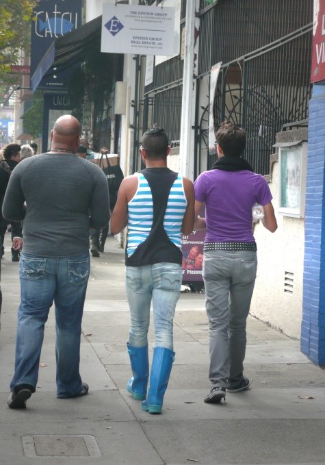 Three men walking down Market Street toward Castro