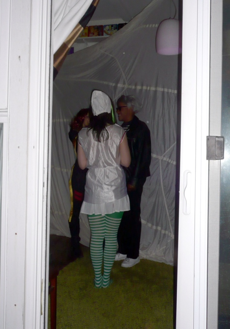 Woman in nurses Halloween costume through doorway