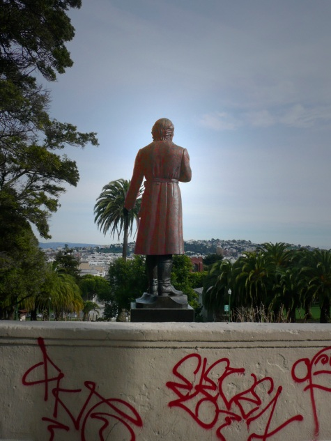 Dolores Park statue from the back with graffiti in the foreground