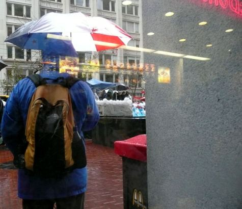 Photograph of man holding umbrella with reflection making him appear headless