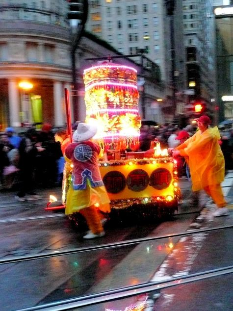 Small weird float being pushed by three characters through the San Francisco Chinese New Year's parade