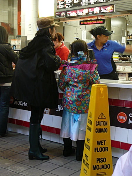 woman and child in line at McDonalds on a rainy day