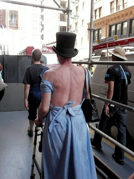 man with walker in backless evening gown and top hat