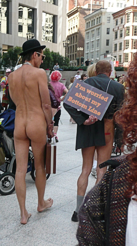 photograph of one naked man and another with just a short coat at st stupids day parade in san francisco