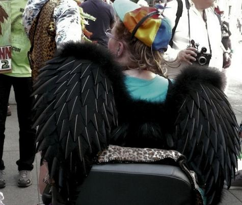 fine art photograph by san francisco artist sarah curtiss of woman in wheel chair with black wings at st stupids day parade