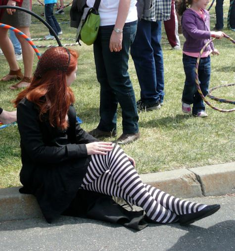 Red haired woman sitting on curb with striped tights