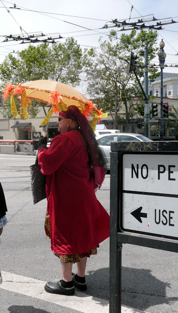 Man in drag with parasol and big feet