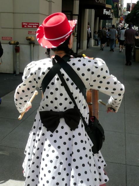woman in red cowboy hat with polka dotted dress walking with bass drum