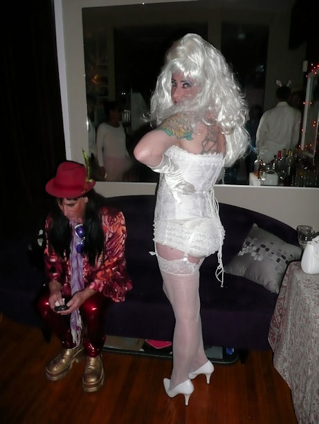 brother k dressed in white corset with huge white wig and white high heels and stockings