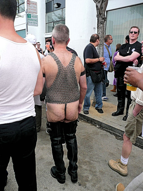 man in butt high black leather boots with metal mesh shirt