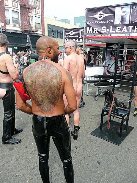 tattooed man in black rubber