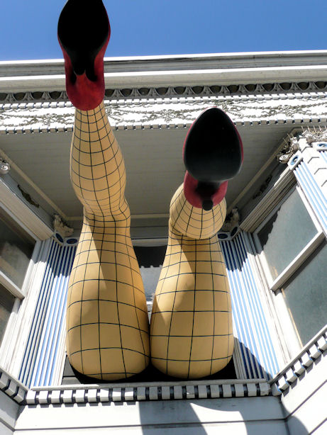 fake legs and butt in fishnet stockings coming out of window on haight street